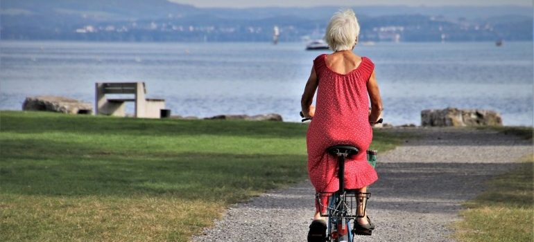 An older woman is riding a bicycle in a park next to the sea, representing activities one can enjoy if one retires in South Point