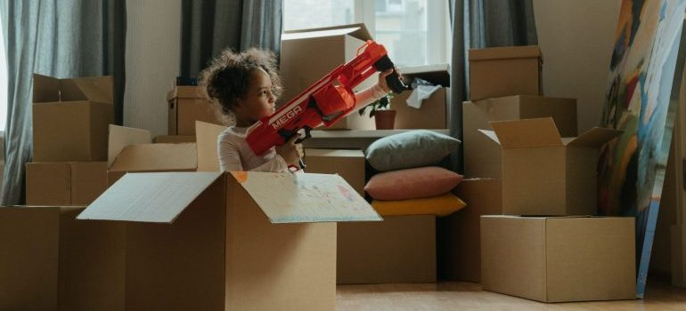 A girl playing with a plastic toy in a cardboard box representing keeping your kids entertained while moving to Coconut Grove