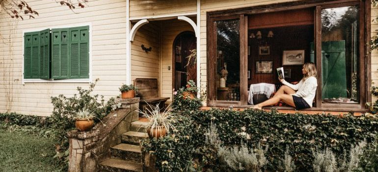 woman sitting on a porch and reading