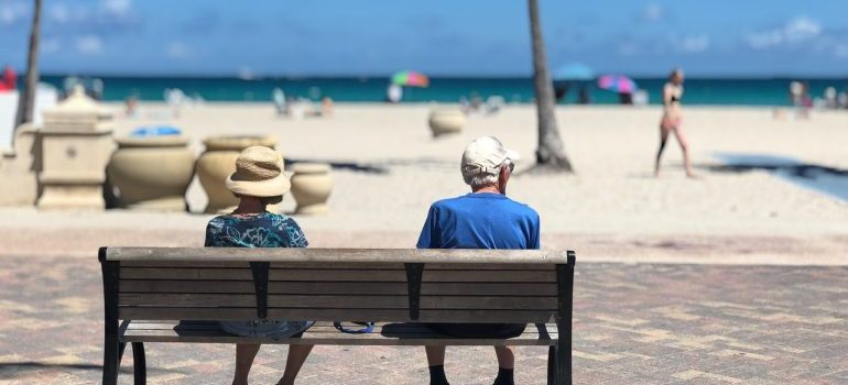A man a a woman sitting on a beach looking onto the beach representing buying a rental property in Boca Raton