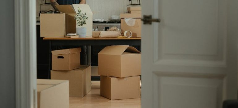 A man packing belongings in moving boxes