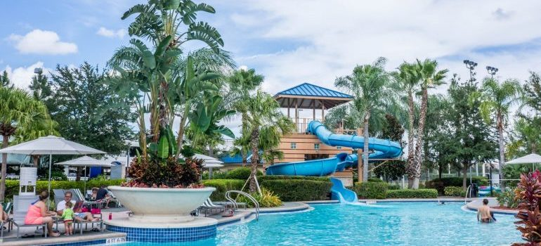 a view onto a waterpark (pool, palm trees and a slide)