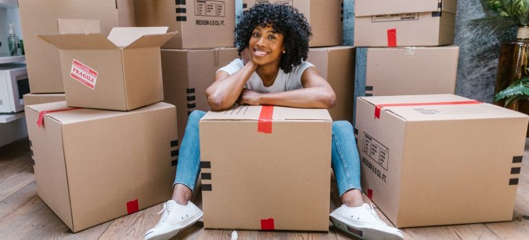 Woman smiling surrounded by boxes
