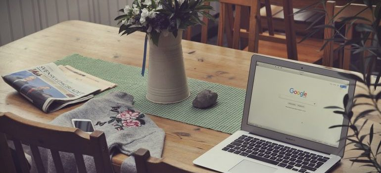 A laptop on a dining table with a flower vase and a newspaper - finding professional movers on short notice