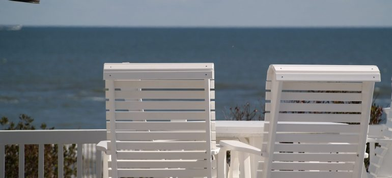 Two white chairs on the balcony with a view to the ocean.
