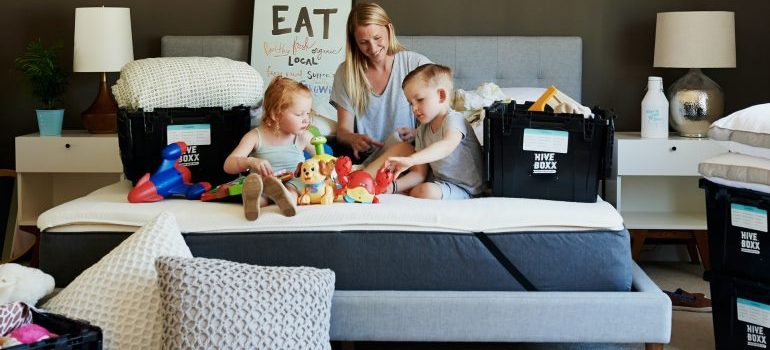 A mother with her 2 kids sitting on a bed - simplify storage bins