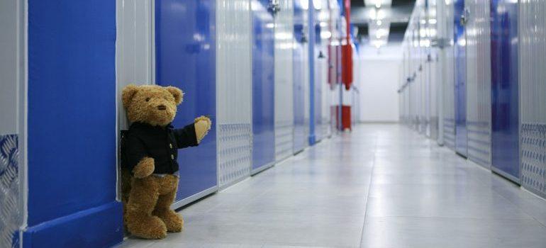 Blue storage units and a teddybear in the hallway.