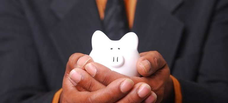 Man in a suit holding a piggy bank