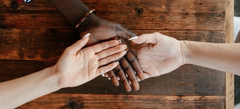 Three hands stacked on top of one another on top of a wooden table