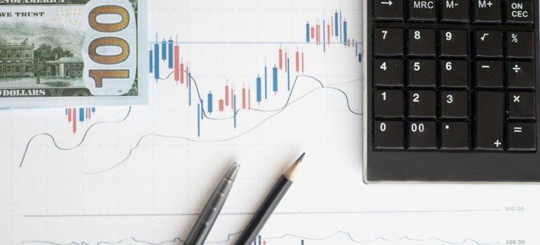 Dollar bill, a chart, pencils and calculator