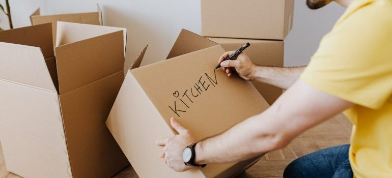 """A man labeling a cardboard box """"kitchen"""" while sitting on the floor"""