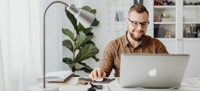 A man sitting at a desk doing work on his laptop