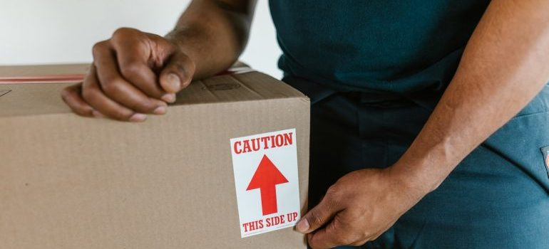 a man holding the box - organize an interstate move