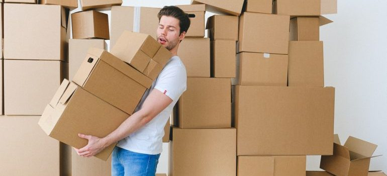 A man carrying cardboard boxes stacked one on top of another, with a lot of boxes behind him as well representing where to store possessions while renovating a home in Fort Lauderdale