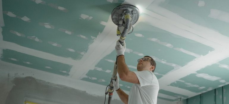 A man is polishing the ceiling while getting ready to prepare your new Boca Raton flat for moving in.