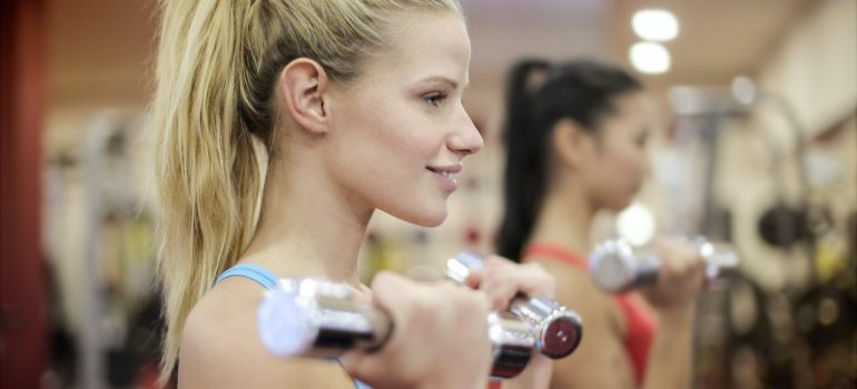 Two girls with ponytails are exercising in the gym with hand weights.
