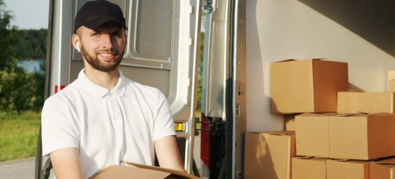 A smiled man holding moving boxes