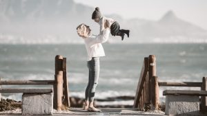 A single parent enjoys with the child on the lake shore.