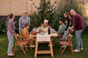A group of people are sitting and standing around a table in the yard, where food for the party has been arranged.